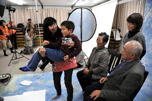 写真:仮設住宅の集会所で撮影に臨む狩野守一さんの家族。写真家の榎並悦子さんは守一さんのひ孫、颯太くんを抱いて笑顔を引き出した=5日、福島県相馬市、渡辺幹夫撮影