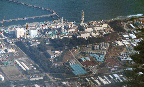 写真:福島第一原発の敷地に並ぶ灰色や青色の汚染水貯蔵タンク。同原発の西方約40キロ、高度約1万3千メートルから撮影した=朝日新聞社機から、堀英治撮影