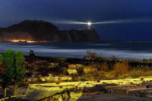 写真:再点灯された塩屋埼灯台。海岸線は家が流され、土台だけが残っていた=30日夕、福島県いわき市、森井英二郎撮影