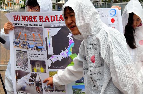 写真:外国人記者に原発について話す福島県出身の円谷さん(中央)=ダーバン、杉山正撮影