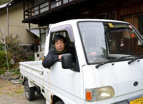 写真:避難生活を共にした軽トラックと秋山さん=11月28日、群馬県藤岡市鬼石、高橋淳撮影