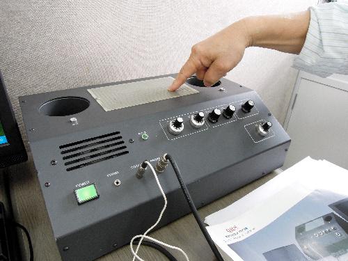 写真:髪の毛を台にのせれば、内部被曝の状態がわかるというQRS装置