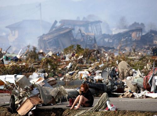 写真:大津波で壊滅的な被害を受けた宮城県名取市閖上(ゆりあげ)地区で、道路に座り込んで涙を流していた伊藤茜さん=2011年3月13日