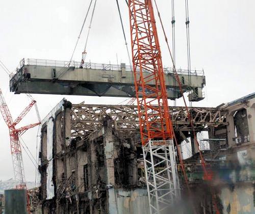 写真:東京電力福島第一原発4号機の天井クレーン撤去作業。天井に据え付けられていた横32メートル、縦10メートルの巨大な枠が地上に下ろされた=5日、東京電力提供