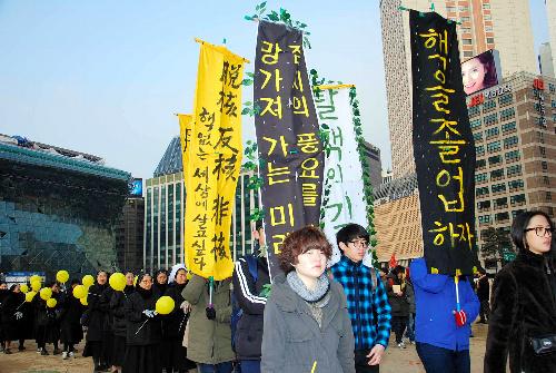 写真:10日、「核から卒業しよう」など脱原発を訴えるのぼりを手にソウルの中心街をデモ行進する集会参加者ら=中野晃撮影