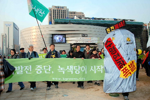 写真:10日、原発運転中断を訴える横断幕を掲げてデモ行進する韓国の「緑の党」の関係者ら=ソウル、中野晃撮影