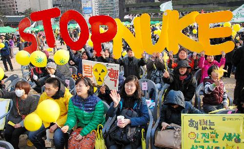 写真:10日、「脱原発」を訴えるプラカードなどを掲げて福島第一原発事故から1年の集会に集まった参加者ら=ソウル、中野晃撮影