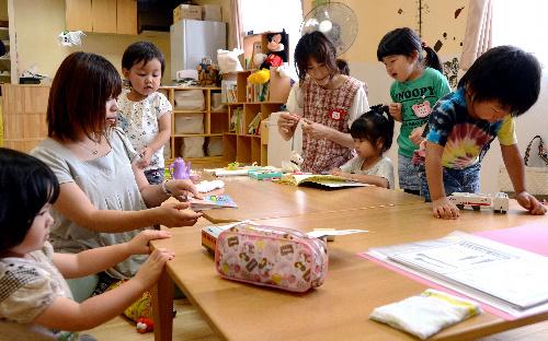 写真:福島県から山形市に母子避難している人たちの交流拠点「ふくしま子ども未来ひろば」。母親たちが一時預かりや読み書き教室を運営、イベントも手がける。遊び相手をするスタッフも避難者だ=20日、山形市香澄町、西村隆次撮影