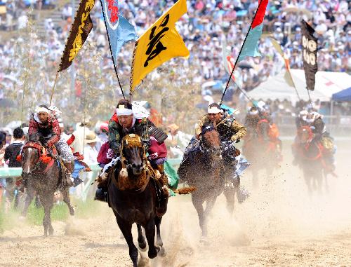 写真:相馬野馬追の甲冑競馬で土煙を上げて競い合う騎馬武者たち=29日午後、福島県南相馬市、日吉健吾撮影