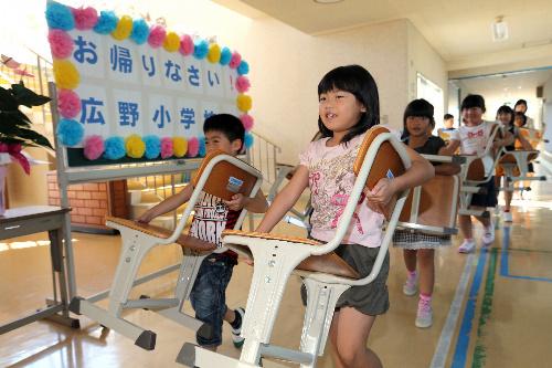 写真:学校が再開し、体育館にいすを運ぶ児童たち=27日午前、福島県広野町、長島一浩撮影