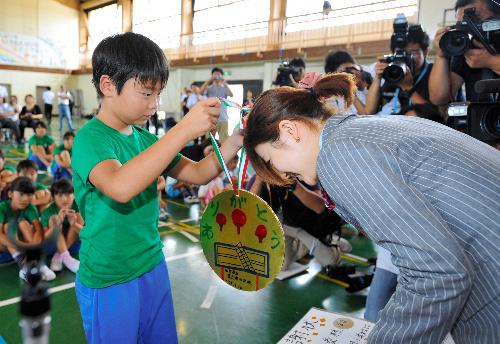 写真:東六郷小学校の児童から手作りの金メダルを受け取る福原愛選手=10日午前、仙台市若林区、浅野哲司撮影