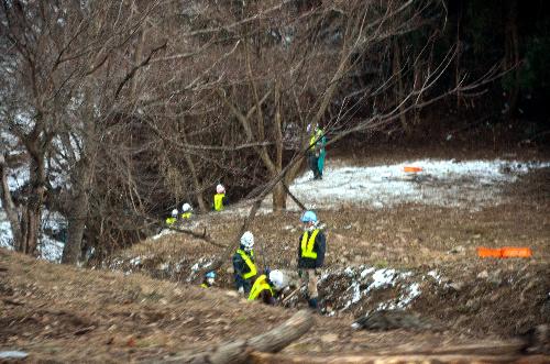 写真:集めた枝や石を川に捨てる作業員=12月11日、田村市
