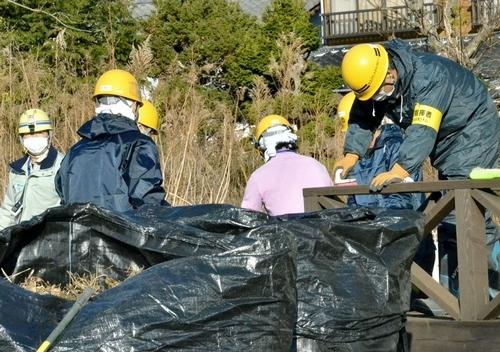 写真:住宅で拭き取りをする作業員たち。手前の黒い袋には草木などが入っている=7日午前9時、福島県楢葉町、青木美希撮影