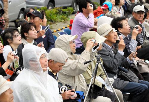 写真:鹿児島県南大隅町の佐多岬で、雲の切れ間から金環日食を観察する人たち=21日午前7時23分、岩下毅撮影