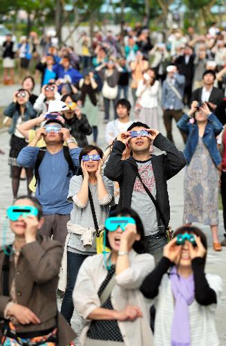 写真:雲の切れ間から金環日食が姿を見せ、歓声を上げて観察する人たち=21日午前7時33分、東京・台場、西畑志朗撮影
