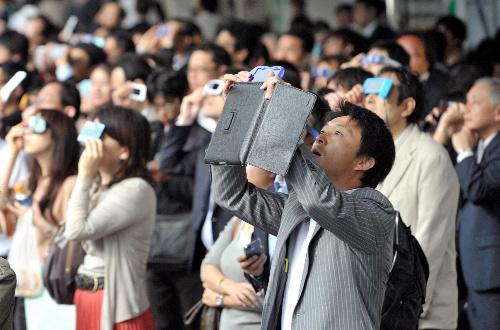 写真:日食を見る通勤途中のサラリーマンら=21日午前7時31分、JR東京駅八重洲口、加藤諒撮影
