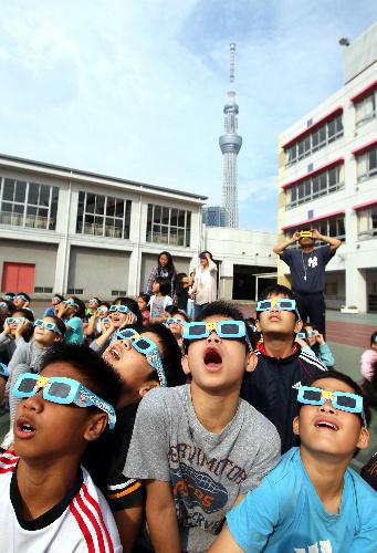 写真:金環日食を観察する押上小学校の6年生たち。後方は22日に開業する東京スカイツリー=21日午前7時30分、東京都墨田区押上3丁目、金子淳撮影
