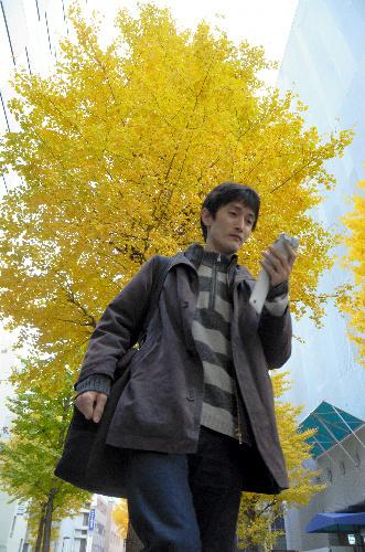 写真:仕事からの帰り道、ツイッターでつぶやく島田暁さん=千代田区