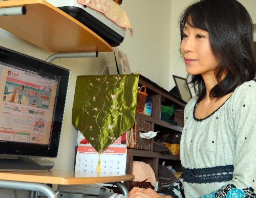 写真:「転勤妻」のサイトの投稿欄をチェックする大向貴子さん=府中市