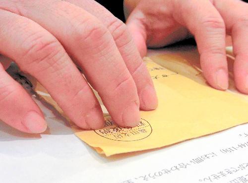写真:児童扶養手当の書類を前に話す母親。介護の仕事のため、爪は短く切りそろえている=大田区