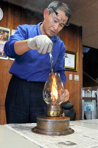 写真:ランプの手入れをする県立青少年研修センターの谷口源太郎さん=鹿児島市宮之浦町