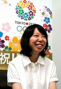 写真:自らデザインした、東京五輪開催を祝うポスターを背にする島峰藍さん。中央の5色のリースが招致ロゴ=東京都庁