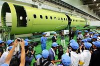 公開されたMRJの胴体の前で質問に答える川井昭陽社長(中央)=2013年9月7日午後、愛知県飛島村