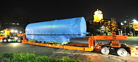 トレーラーで運ばれるMRJの胴体。背景の愛知県庁(右)と名古屋市役所(中央)は特別にライトアップされた=2013年10月13日午前2時45分、名古屋市中区