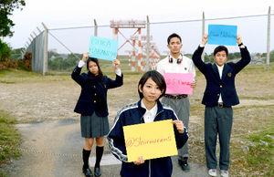 写真:普天間飛行場のフェンス前で、自分のソーシャルメディアのアカウントを書いた色紙を掲げる地元の高校生たち。左から仲西櫻樺さん、志村早紀さん、山城周さん、上原男さん=沖縄県宜野湾市、関口聡撮影