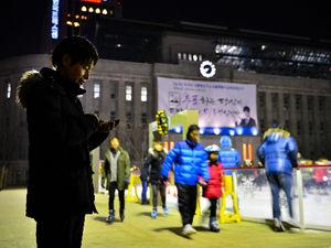 写真:ソウルでツイッターを発信し続ける武田肇記者。奥は日本の植民地時代に建てられたソウル市旧庁舎=17日夜、韓国・ソウル、水野義則撮影