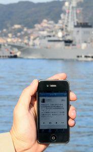 写真:「明後日より、広島に旅立ちます」などと書かれた海上自衛官のつぶやき。奥は出港する護衛艦=長崎県佐世保市、西畑志朗撮影(画像の一部を修整)