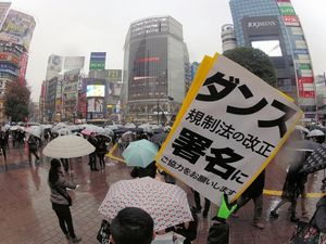 写真:風営法の改正に向け、雨の街頭で署名を集める男性=東京都渋谷区、関口聡撮影