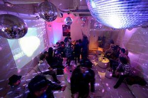 写真:深夜のクラブで、DJ(左奥)が選曲する音楽を楽しむ人たち=東京都港区、関口聡撮影
