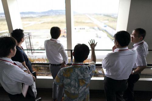 写真:県職員の案内で沖縄IT津梁パークを視察する人々=沖縄県うるま市、矢木隆晴撮影
