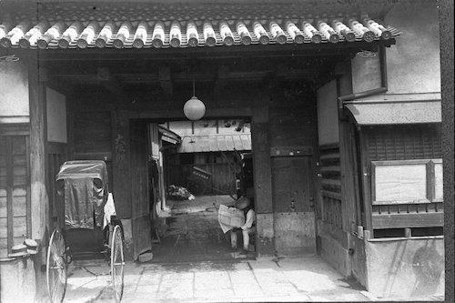 写真:明治40年代の朝日新聞社通用門。専属車夫の帳場がここにあった。新聞発送もこの門から行われた。右側は新聞掲示板