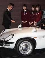 「コスモスポーツ」の説明を受ける(右から)高山一実、永島聖羅、衛藤美彩