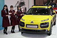 車両保護用の樹脂パーツを装備した「C4カクタス」と記念撮影する(左から)深川麻衣、斉藤優里、秋元真夏