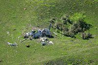 空爆でできたクレーターがいくつもある草原の中に残された朽ちた零戦。風雨にさらされたためか、まるで白骨のように機体を草原に横たえていた=8月27日、北マリアナ諸島・パガン島、朝日新聞社機「あすか」から、