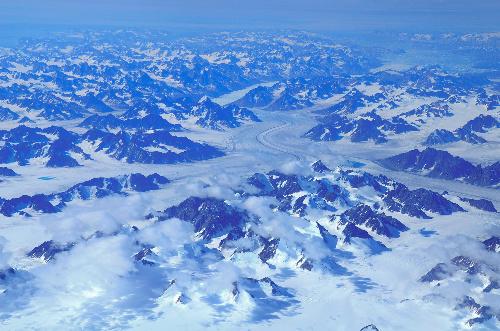 写真:上空からのグリーンランド南部。雪をまとった山々の間を氷河が流れる=6月30日、中山由美撮影