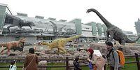 動く恐竜モニュメントを見る人たち=2015年3月7日、福井市のJR福井駅西口駅前広場、筋野健太撮影