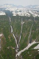 雪が残る滝つぼに水しぶきを上げて落ちるハンノキ滝(中央)。同じ滝つぼに落ちる左の称名滝と合わせてV字に見える=5月28日午後、富山県立山町、朝日新聞社ヘリから、橋本弦撮影
