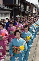 良縁願って「丸まげ祭」。丸まげ姿で歩く女性たち=2015年4月17日、富山県氷見市、寺脇毅撮影