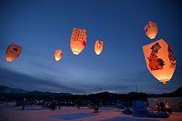 夕暮れの雪原に浮かぶ色とりどりの巨大紙風船=2015年2月7日、南砺市、筋野健太撮影