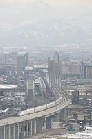 北陸新幹線開業初日、金沢方面から富山駅(後方)に向かう北陸新幹線。後方は立山連峰=2015年3月14日、富山市、筋野健太撮影