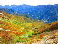 見ごろを迎えた紅葉。立山ロープウェイ(左上に大観峰)、黒部湖(中央右)が見え、奥に後立山連峰がそびえる=2015年9月30日、富山県立山町、三島庸孝撮影