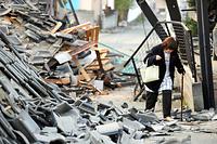 屋外の避難所で一夜を過ごし、住宅が倒壊した道路を歩いて自宅に戻る国武ちどりさん(62)。「『ドンッ』と突き上げられ、横にも揺さぶられ、怖くて動けなかった」=15日午前6時33分、熊本県益城町宮園、長島