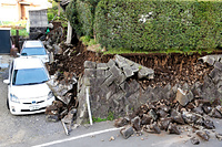 崩れた石垣につぶされた車=15日午前7時5分、熊本県益城町、小宮路勝撮影