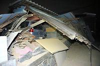 倒壊した屋根に押しつぶされる車=15日午前3時10分、熊本県益城町、上田幸一撮影