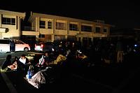 公民館の駐車場に避難した人たち=15日午前0時51分、熊本県益城町、上田幸一撮影