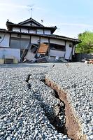 倒壊家屋へ向かって真っすぐのびるひび割れ=15日午前7時54分、熊本県益城町惣領、日吉健吾撮影